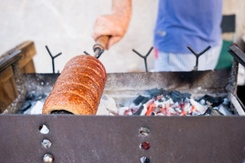 Stäng sig upp av mannen som lagar mat och bakar sött romanian horn- bröd som är bekant som Kürtös kalács i utomhus- gatamatmarkna arkivfoto