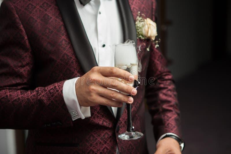 Stäng sig upp av mannen som rymmer ett exponeringsglas av champagne i hand royaltyfria bilder