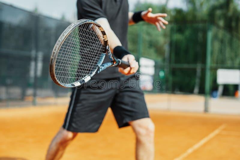 Stäng sig upp av mannen som spelar tennis på domstolen och slår bollen med en racket arkivbild