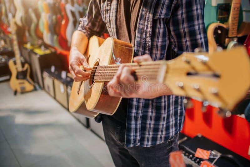 Stäng sig upp av mannen som står och spelar på den akustiska gitarren Han klär upp som hipster Grabben är bara i rum arkivbilder