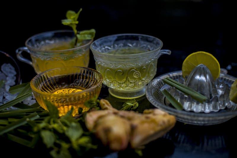 Stäng sig upp av med is te för citrongräs i en genomskinlig kopp på träyttersida med rått grönt te för citrongräs i en kopp och e arkivbilder
