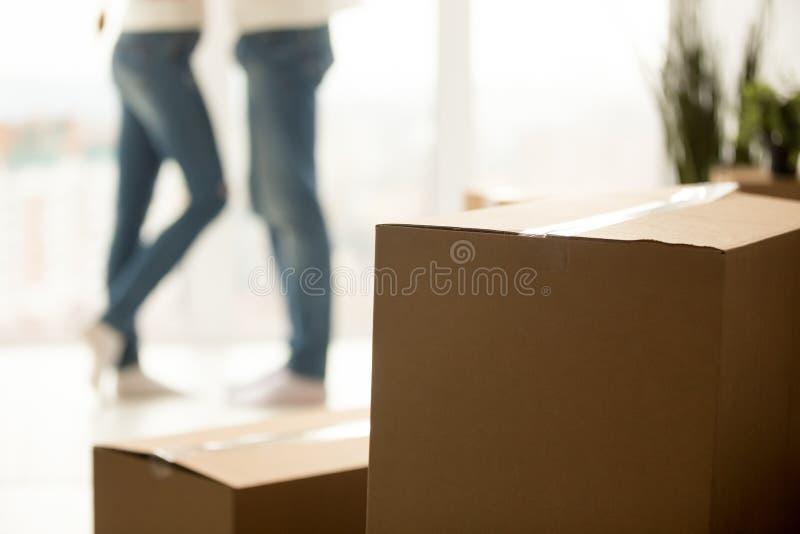 Stäng sig upp av millennial par som flyttar sig till det nya hemmet med askar royaltyfria foton