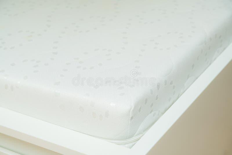 Stäng sig upp av minnesskummadrassen på sängramen på sovrum Komfort som väljer madrassen royaltyfri bild