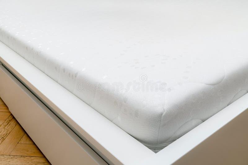 Stäng sig upp av minnesskummadrassen på sängramen på sovrum Komfort som väljer madrassen royaltyfri fotografi