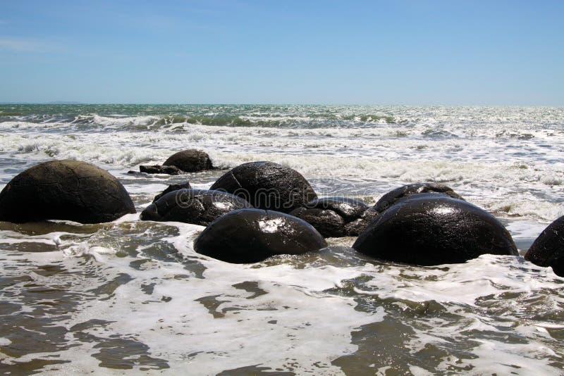 Stäng sig upp av Moeraki sfäriska stenblock av mudstone på stranden som tvättas av bränning av havet, den Koekohe stranden, Pebbl royaltyfri fotografi