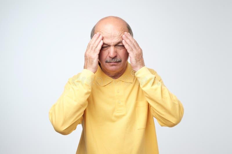 Stäng sig upp av mogen man i gul tshirt med stängda ögon som trycker på hans huvud smärtar in hälsa royaltyfri bild