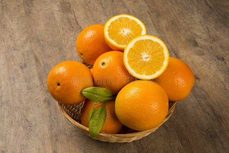 Stäng sig upp av några apelsiner i en korg över en träyttersida arkivfoton
