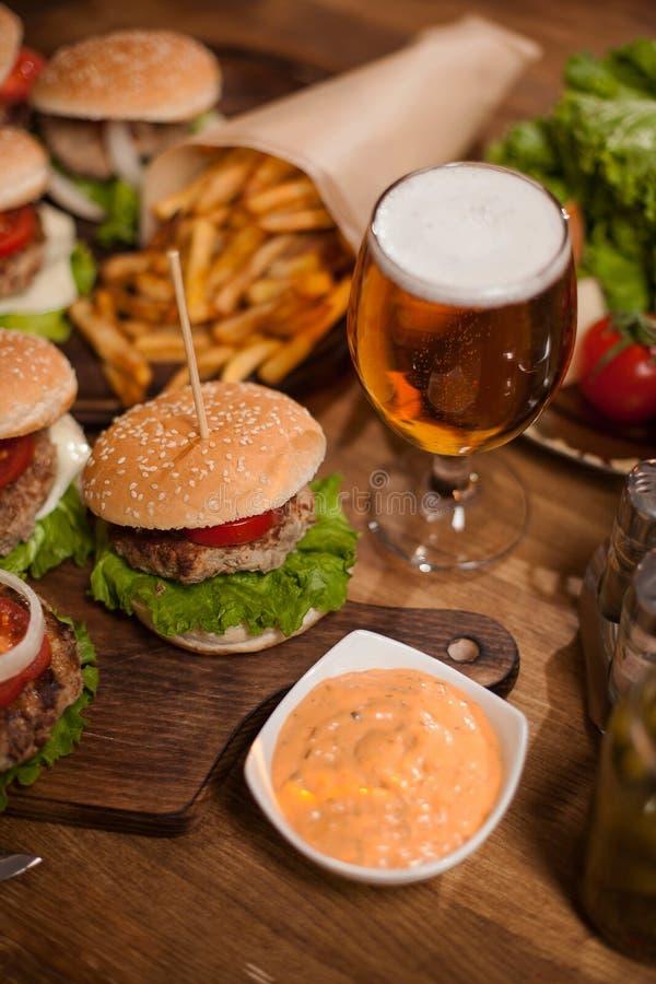 Stäng sig upp av nötkötthamburgaren och öl på en restaurangtabell royaltyfri fotografi