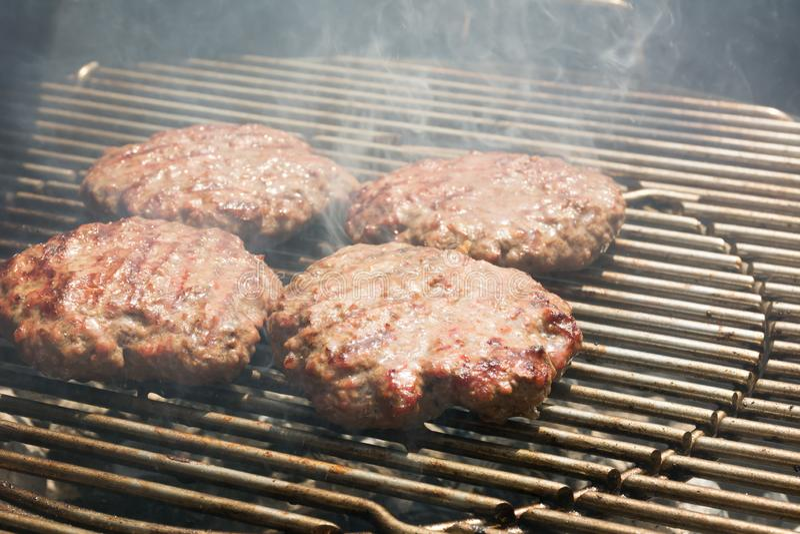 Stäng sig upp av nötkötthamburgaren som lagar mat på ett kolgaller arkivfoto