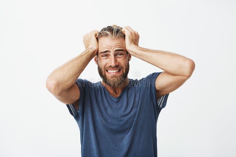 Stäng sig upp av olycklig stilig grabb med hållande hår för skägget med händer och att vara toppet besviket om brutet nytt royaltyfri fotografi