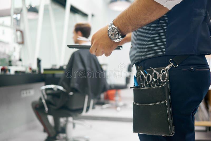 Stäng sig upp av påse för läder för barberare` s liten med metallisk skarp sax royaltyfri foto