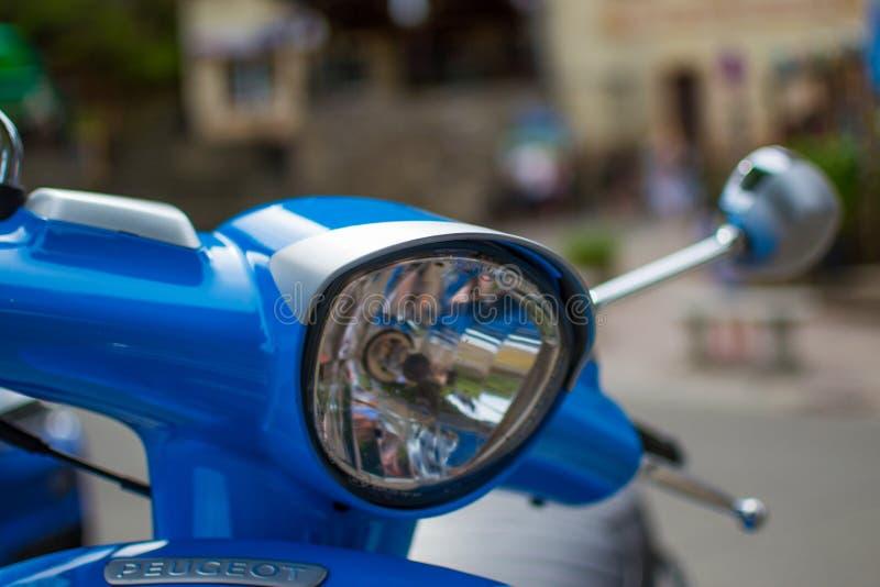 Stäng sig upp av pannlampan av en blå klassisk sparkcykel med defocused bakgrund arkivfoto