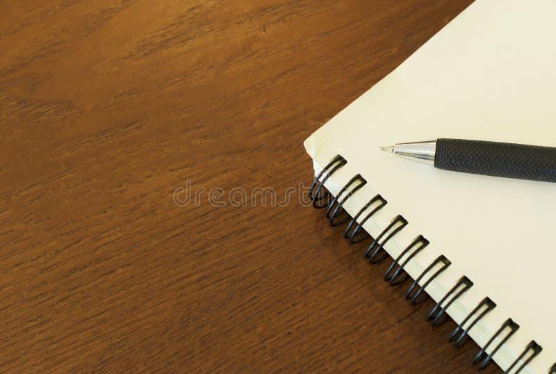 Stäng sig upp av penna med den tomma sidan för anteckningsboken på trätabellbakgrunder fotografering för bildbyråer