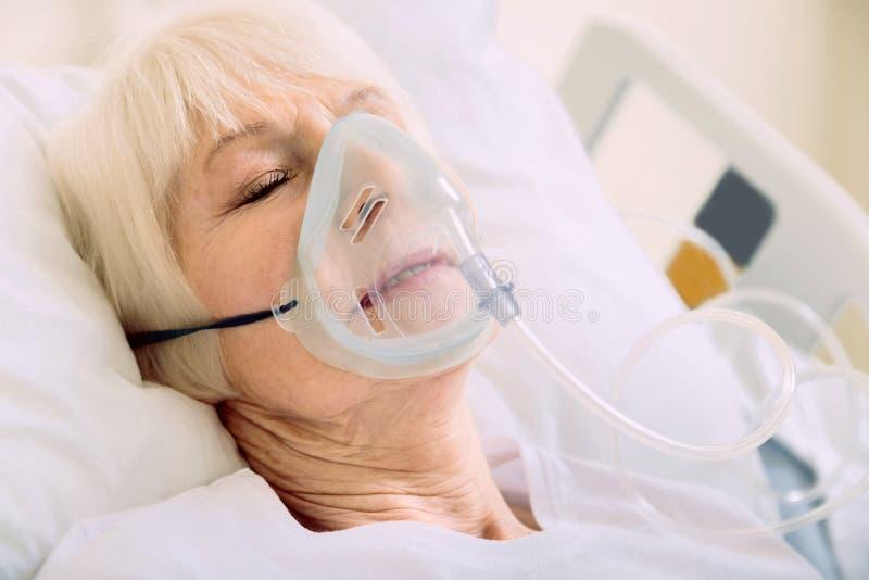 Stäng sig upp av pensionerad dam med respiratorisk service på sjukhuset royaltyfri bild