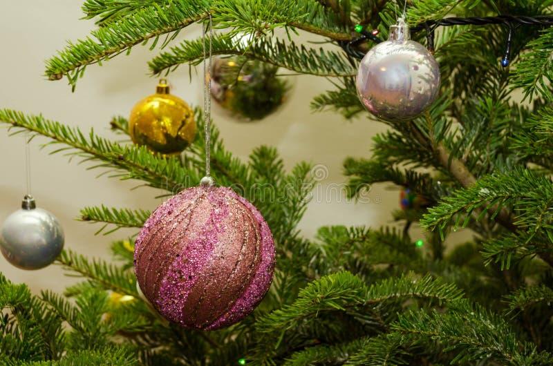 Stäng sig upp av purpurfärgad guld och gråna julgrangarneringar arkivfoton