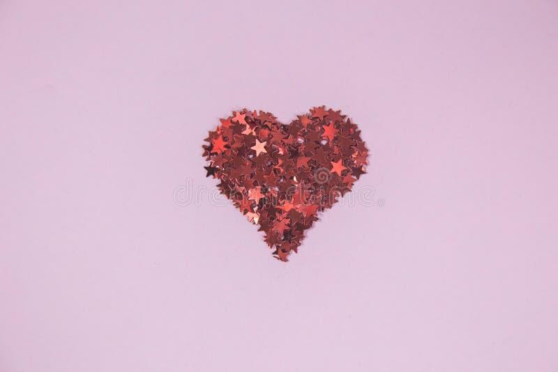 Stäng sig upp av röd hjärta som göras av konfettier i form av den röda stjärnan royaltyfri bild