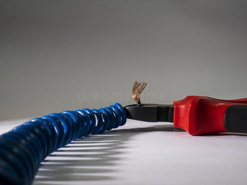 Stäng sig upp av röd plattång och blå vriden tråd på vit bakgrund Plattång som klipper kabel arkivfoto