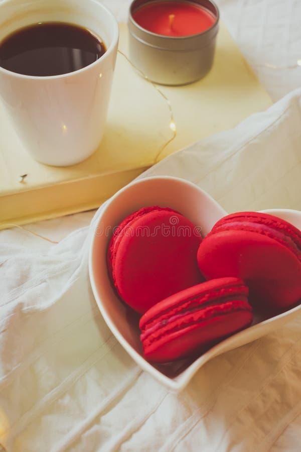 Stäng sig upp av röda macarons i en hjärta formad bunke, bok, stearinljus och ett kaffe royaltyfri bild