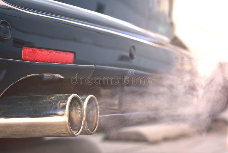 Stäng sig upp av rökiga dubbelavgasrörrör från en startande diesel- bil royaltyfri foto