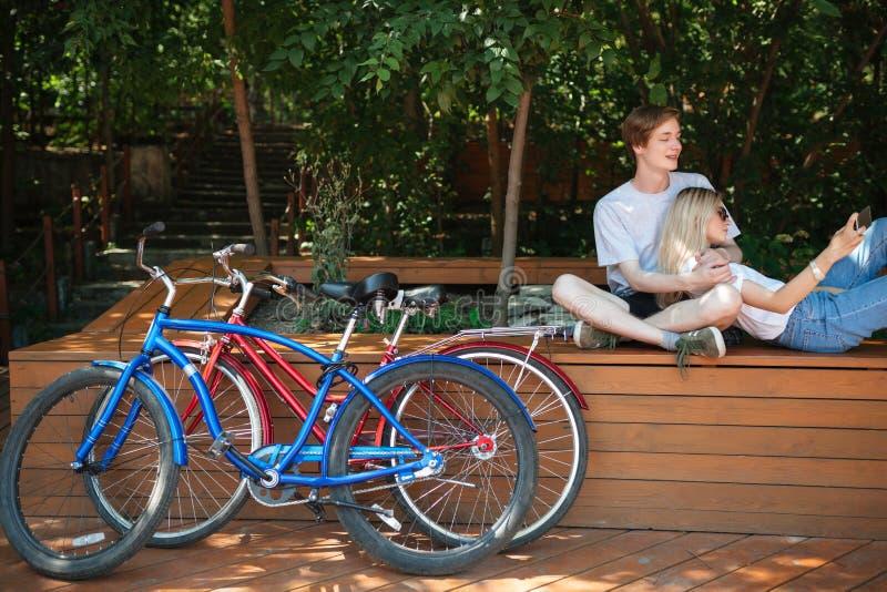 Stäng sig upp av rött, och blåa cyklar parkerar in Pojkesammanträde på bänk parkerar in på med den nätta flickan med blont hår de arkivfoto