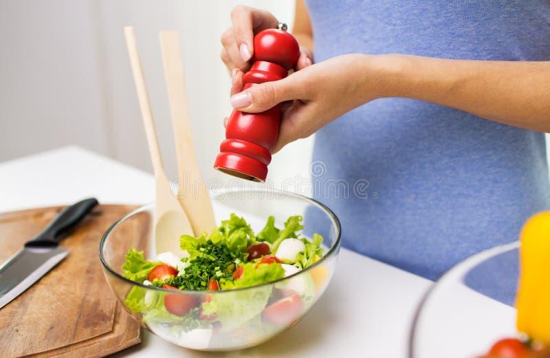 Stäng sig upp av sallad för kvinnamatlagninggrönsaken hemma arkivbilder