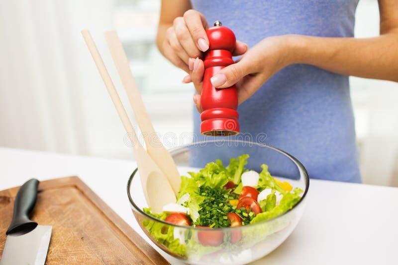 Stäng sig upp av sallad för kvinnamatlagninggrönsaken hemma arkivfoto