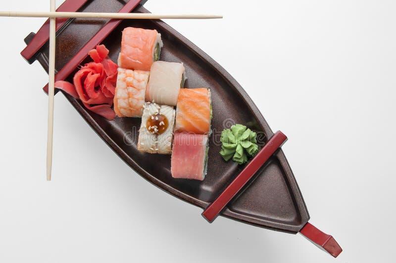 Stäng sig upp av sashimisushiuppsättning med pinnar och sojabönor på ett tjänande som fartygmagasin royaltyfria foton