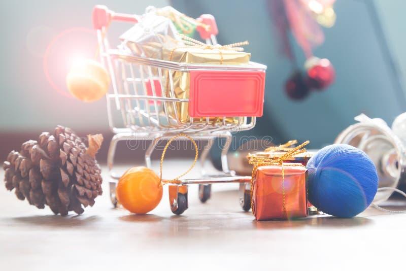 Stäng sig upp av shoppingvagnen med gåvaaskar och julpynt royaltyfria bilder