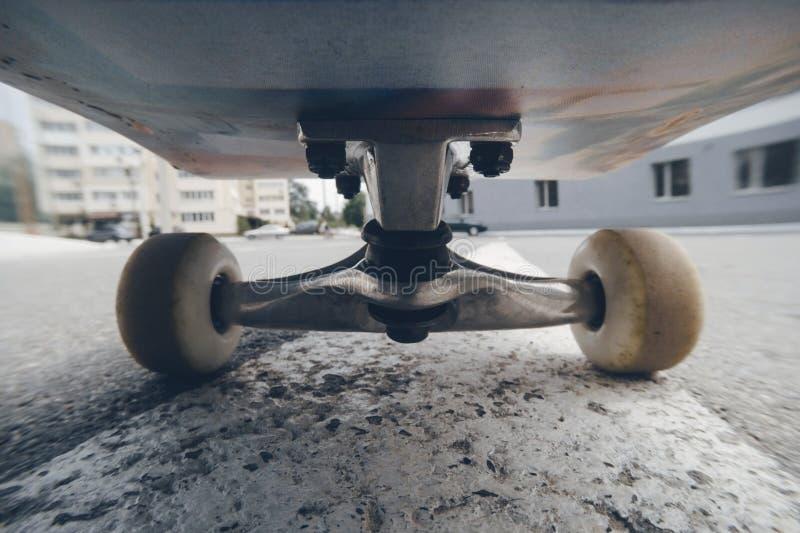 Stäng sig upp av skateboarden på stadsvägmarkering royaltyfri bild