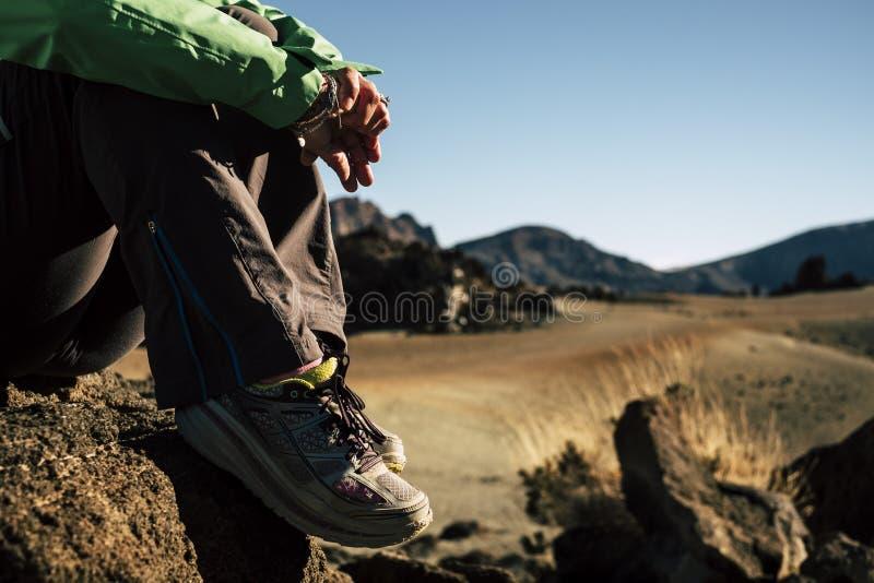 Stäng sig upp av skofotvandraren som vilar och kopplar av under utomhus- trekking fritidsaktivitet på berget - utrustning för van arkivfoton