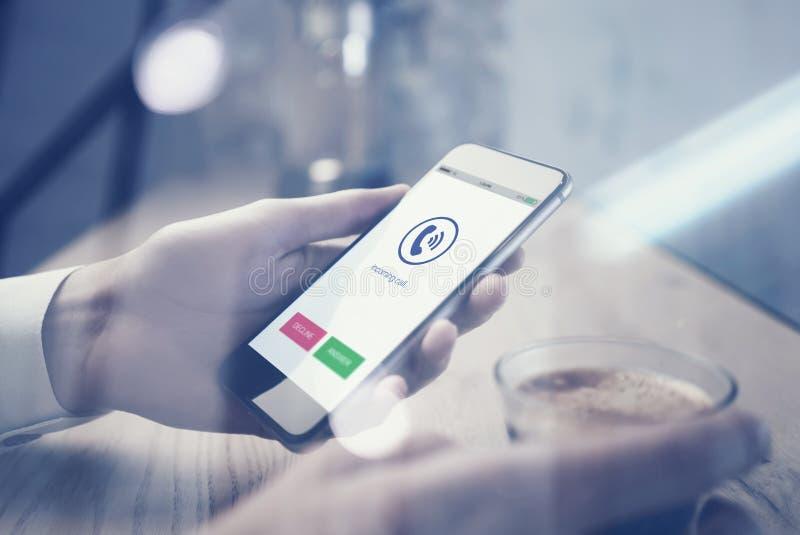 Stäng sig upp av smartphoneinnehav i kvinnlig hand Koppespresso på tabellen som är horisontal Telefon som kallar symbolsskärmen fotografering för bildbyråer
