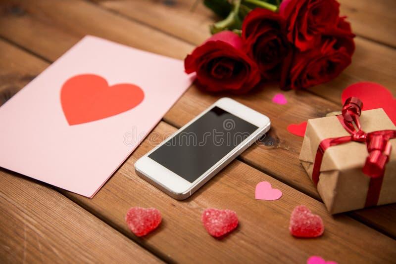Stäng sig upp av smartphonen, gåvan, röda rosor och hjärtor arkivbild