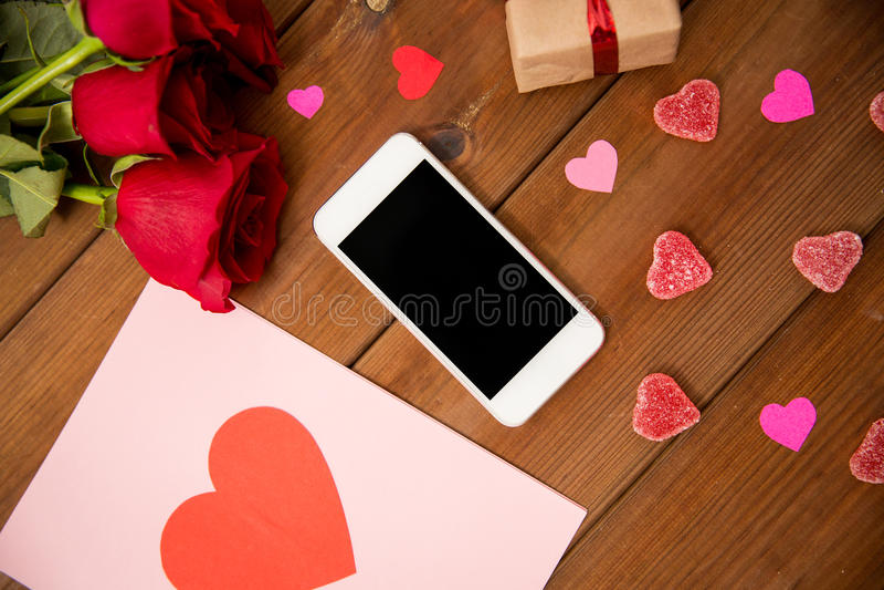 Stäng sig upp av smartphonen, gåvan, röda rosor och hjärtor arkivbilder