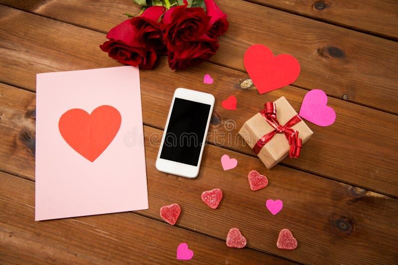 Stäng sig upp av smartphonen, gåvan, röda rosor och hjärtor arkivfoton