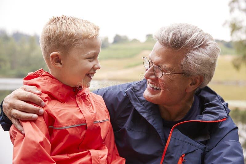 Stäng sig upp av sonson och hans farfar i bygden som ser de, ståenden, sjöområdet, UK arkivbilder