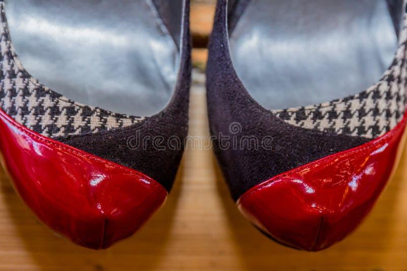 Stäng sig upp av spetsen av ett par av skor med en kombination av svart, rött och vitt på ett parkettgolv arkivbild