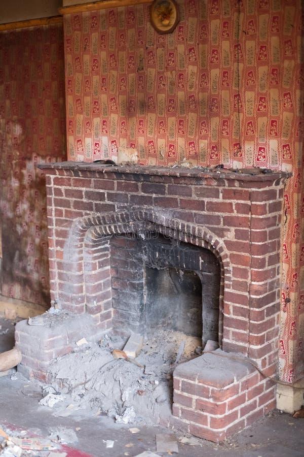 Stäng sig upp av spisen i övergivet hus, med tapeten som skalar av väggen Harv UK royaltyfri fotografi