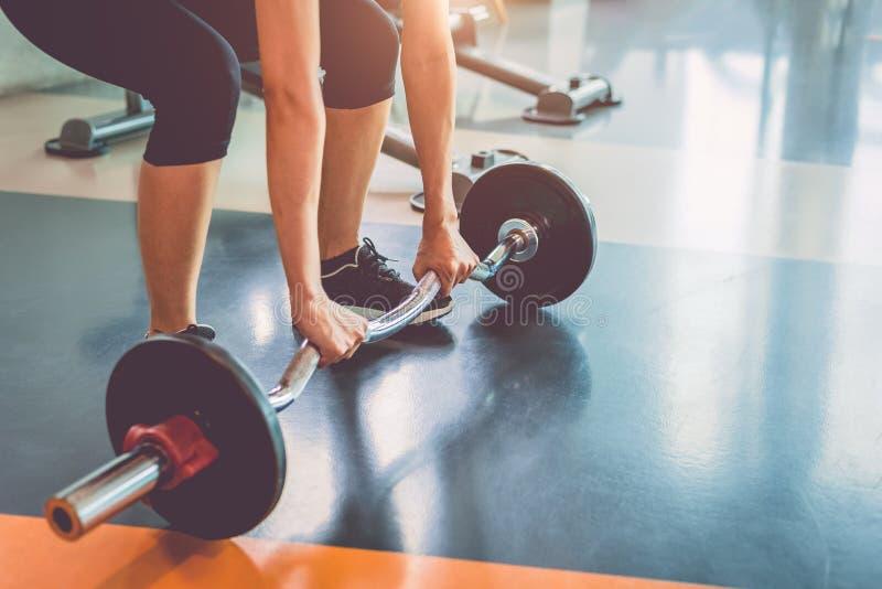 Stäng sig upp av sportkvinnalyftande vikt i konditionidrottshall Genomk?rare?vning och kroppuppbyggnadbegrepp Sund skivstång som  arkivbilder