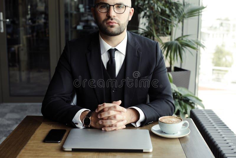 Stäng sig upp av stilig affärsman och att arbeta på bärbara datorn i restaurang arkivfoto