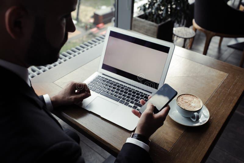 Stäng sig upp av stilig affärsman och att arbeta på bärbara datorn i restaurang royaltyfri foto