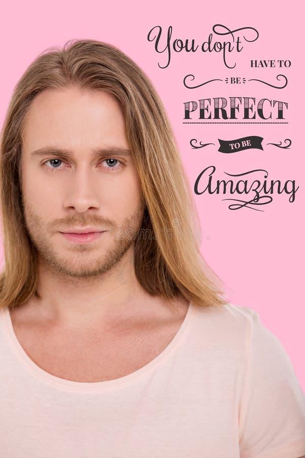 Stäng sig upp av stilig ljus haired man mot rosa bakgrund royaltyfria foton