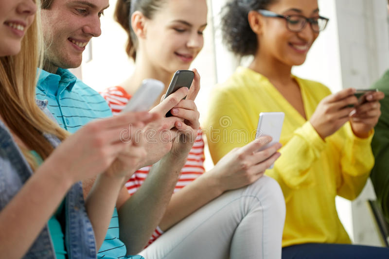 Stäng sig upp av studenter med smartphones på skolan fotografering för bildbyråer