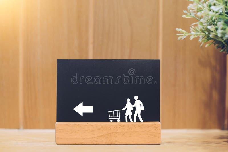 Stäng sig upp av svart tavla med familjen och spårvagnen för att shoppa på en träbakgrund arkivbild