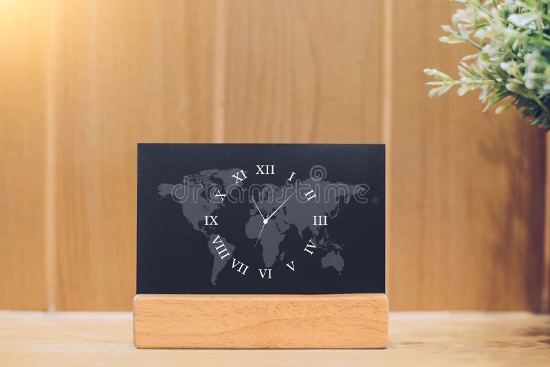 Stäng sig upp av svart tavla med klockan på en världskarta på en träbakgrund arkivfoton