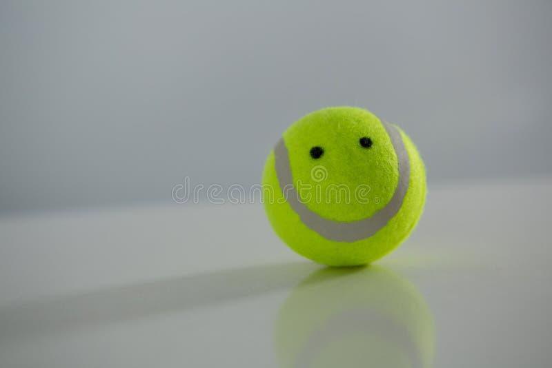 Stäng sig upp av tennisboll med den anthropomorphic framsidan arkivbilder