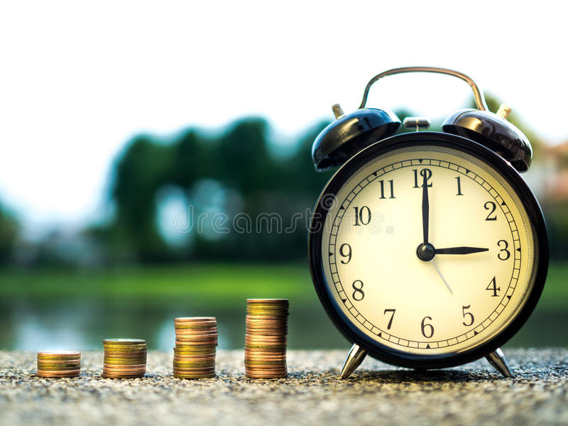 Stäng sig upp av tid- och buntpengarmynt, tidvärde av pengarbegreppet i affärsfinanstema framtida pengarsparande arkivfoton