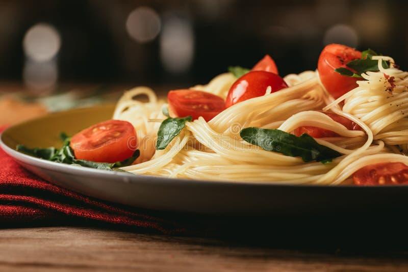 stäng sig upp av traditionell italiensk pasta med tomater och arugula arkivbild