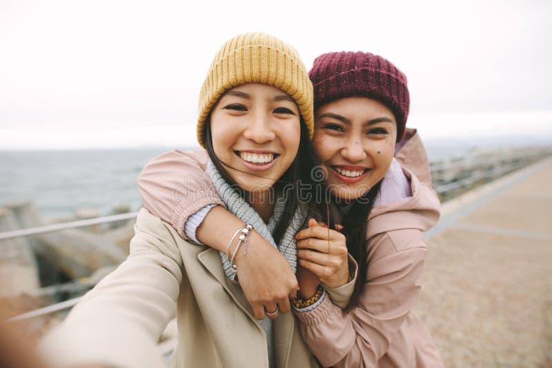 Stäng sig upp av två asiatiska kvinnor som tillsammans utomhus står royaltyfri foto