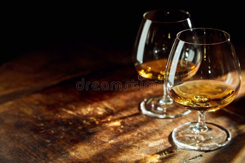 Stäng sig upp av två bourbon fyllda exponeringsglas på tabellen arkivbilder