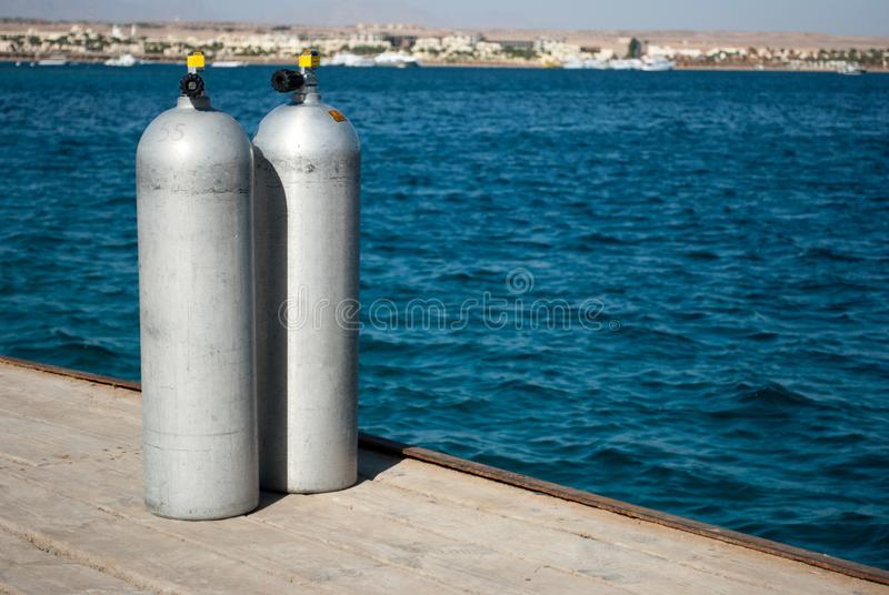 Stäng sig upp av två dykapparatbehållare som står inte långt från vattnet arkivbild